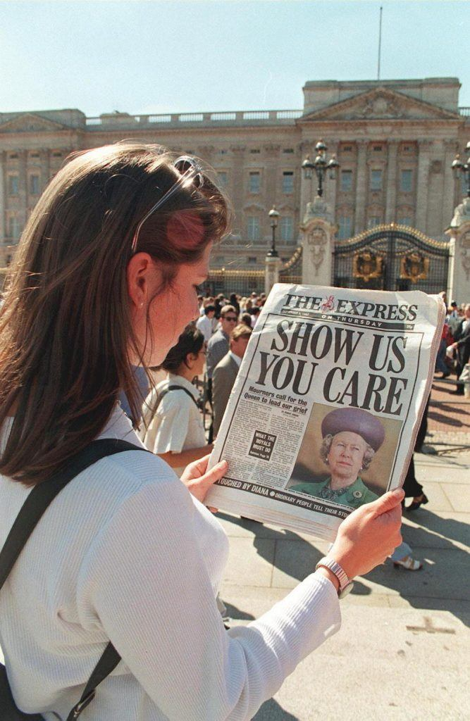 Outside Buckingham Palace, a Londoner reads headlines criticizing the Queen's silence since Princess Diana's death