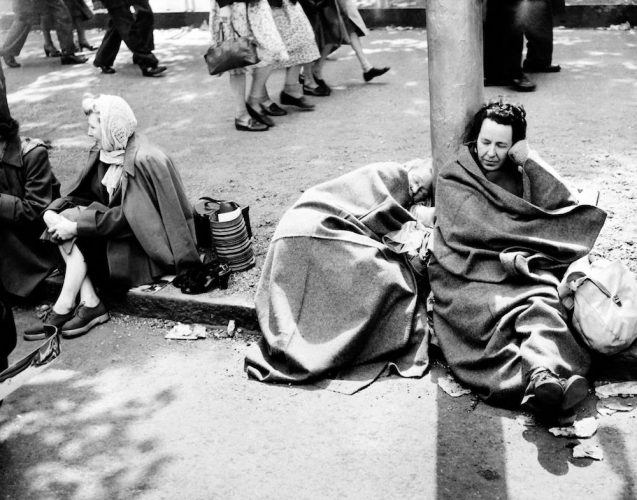 People wait on the royal route on the eve of Britain Queen Elizabeth II's coronation
