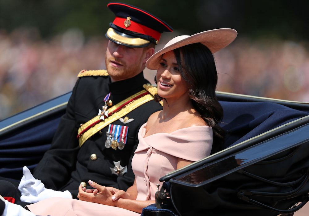 Prince Harry and Meghan Markle ride in a horse-drawn carriage