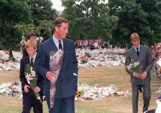 Prince Harry and Prince William collect floral tributes to their mother, Diana, Princess of Wales, from the crowd at Kensington Palace