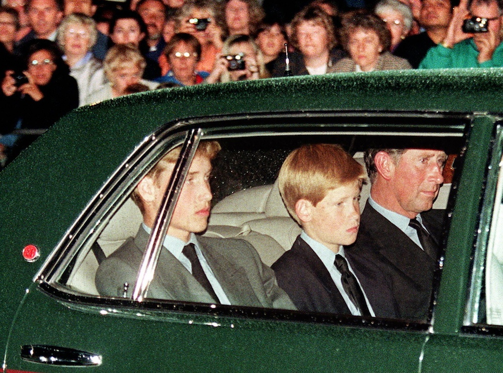 Prince William, Prince Harry, and Prince Charles follow the hearse in a limousine the night before Princess Diana's funeral