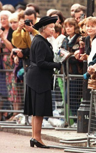 Queen Elizabeth II walks along the rows of wellwishers, receiving flowers and messages outside St. James' Palace
