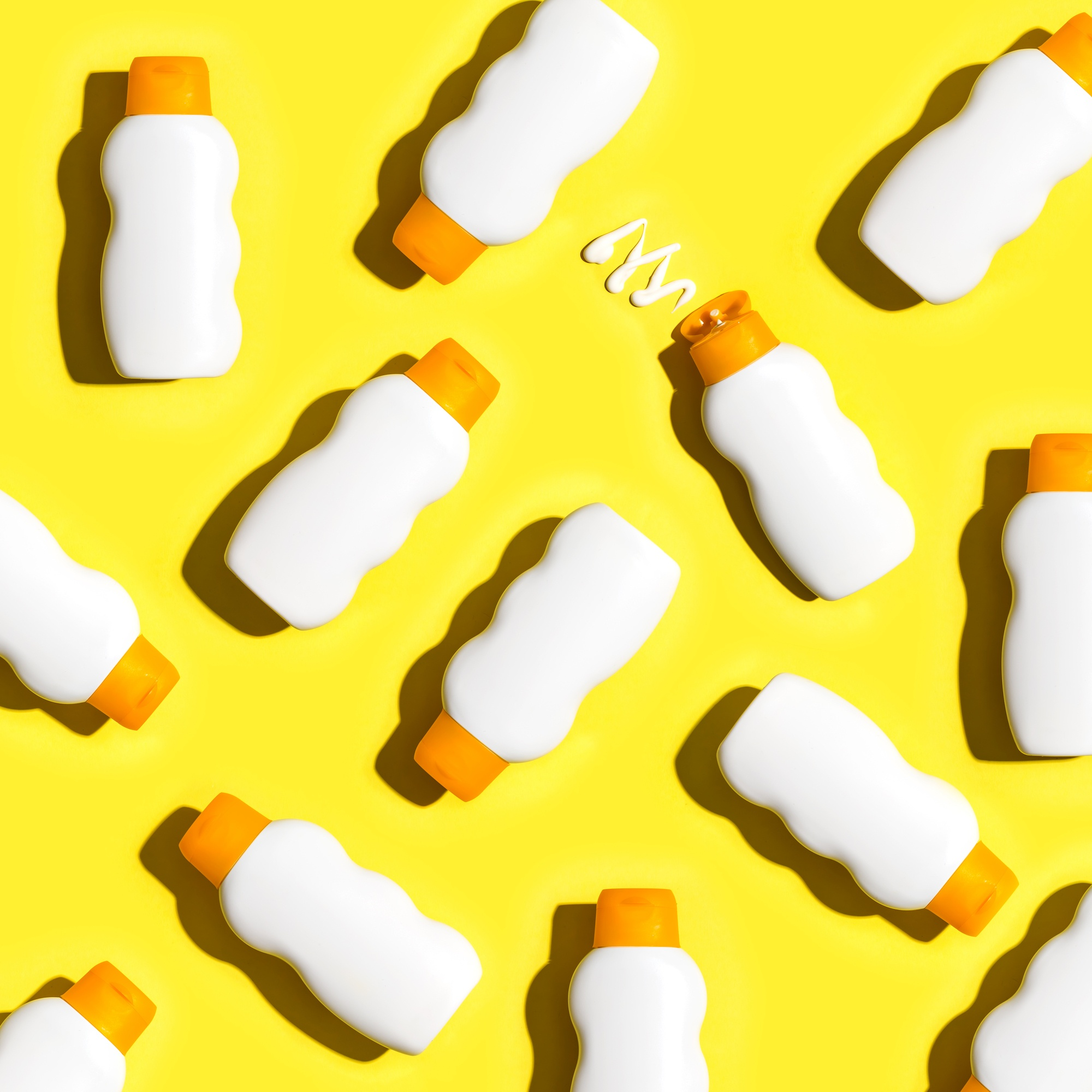 Sunscreen bottles arranged on a bright yellow background