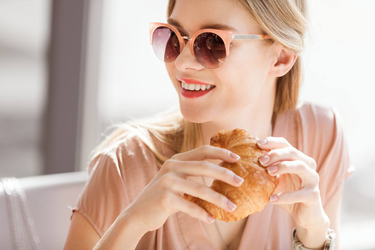 Young woman eating a croissant at a cafe