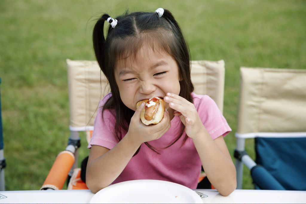 Girl eating a hot dog