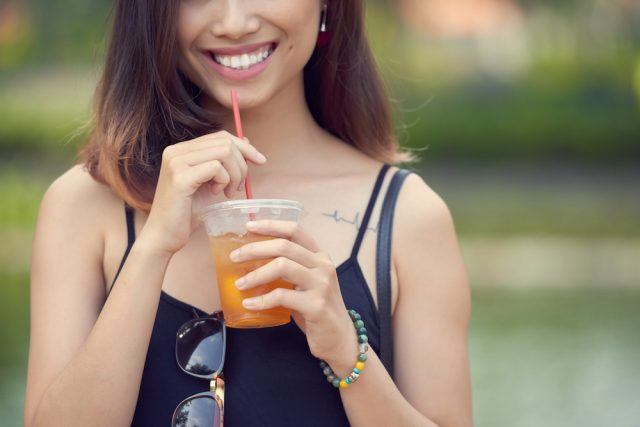 Woman holding cup of iced tea