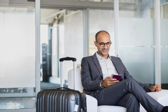 A traveler uses his smartphone at the airport