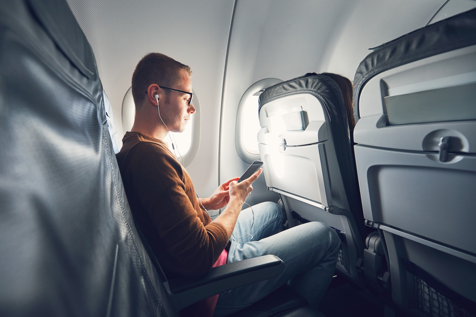 Airplane passenger listens to music on his phone