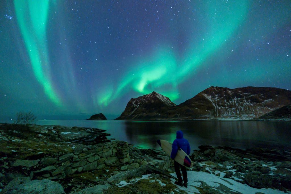 A surfer looks at Northern Lights on March 9, 2018, in Utakleiv, northern Norway