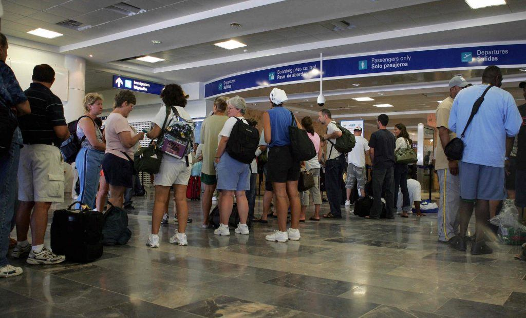 Foreign tourists await the departure of their flights, at the Cancun Terminal 2 airport