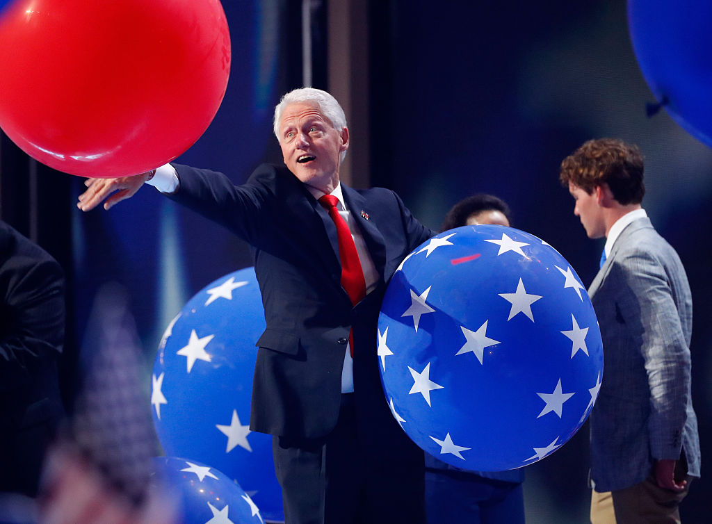 Former US President Bill Clinton plays with balloons