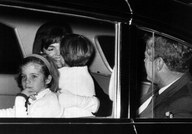 First Lady Jackie Kennedy is greeted by her children after arriving from a trip