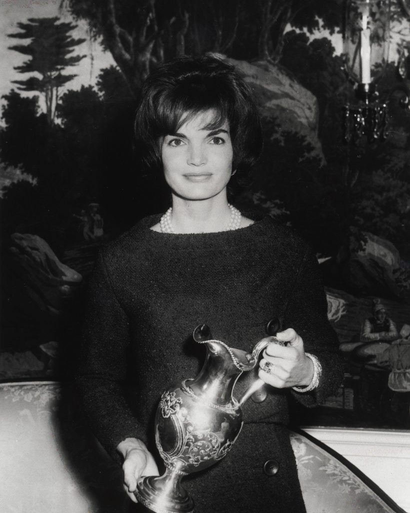 First Lady Jacqueline Kennedy poses for a photograph while holding a gift