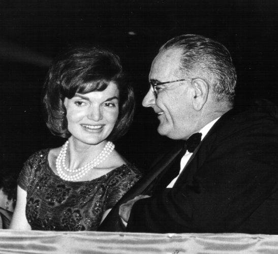 First Lady Jackie Kennedy speaks with Vice President Lyndon B. Johnson during a ceremony January 18, 1963 in Washington, DC