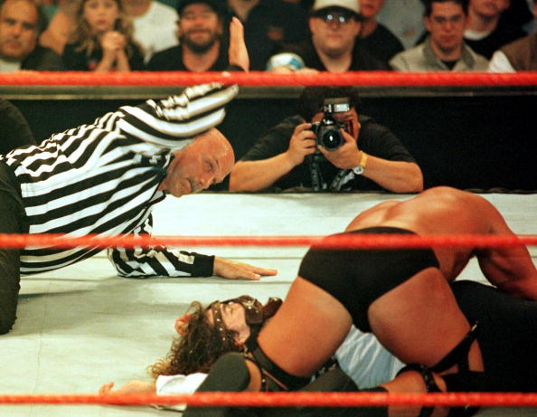 Minnesota Governor, former professional wrestler and guest referee Jesse Ventura (L) administers the three count