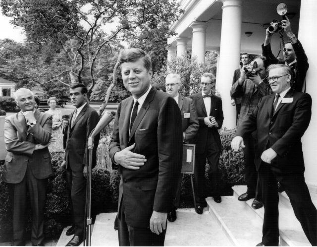 John F. Kennedy laughs with reporters after a White House press conference