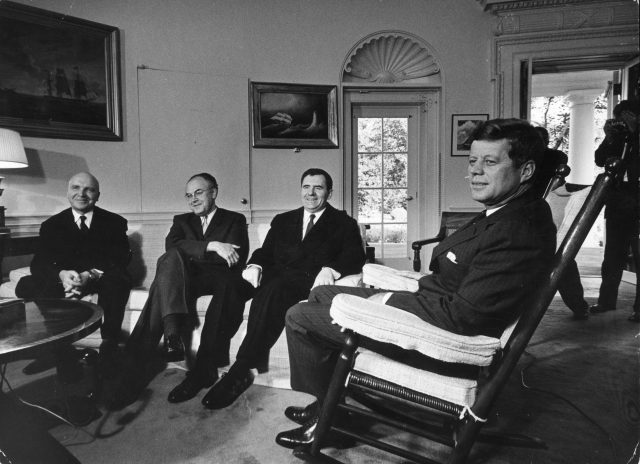 John F. Kennedy sits in a rocking chair in the Oval Office