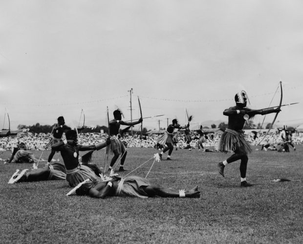 Local people in the Torres Strait Islands perform a war dance in front of Queen Elizabeth II and Prince Philip