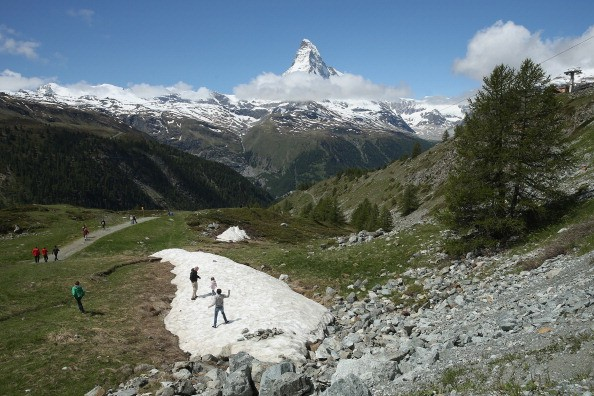 Visitors walk on snow as the Matterhorn stands behind