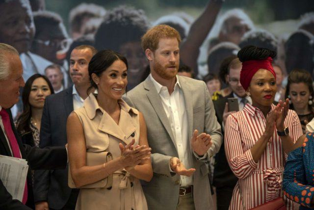 Prince Harry, Duke of Sussex and Meghan, Duchess of Sussex gesture during a visit to the Nelson Mandela Centenary Exhibition, which explores the life and times of Nelson Mandela