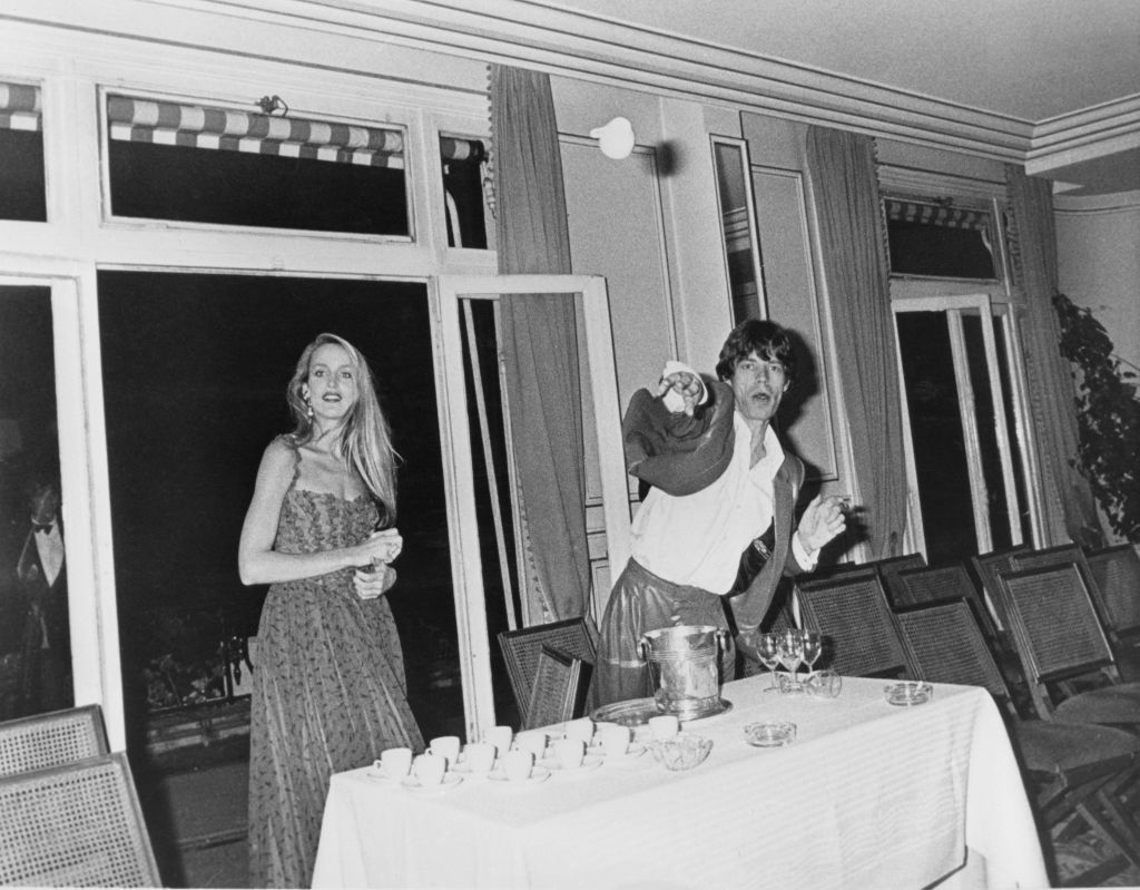 Singer Mick Jagger of The Rolling Stones reacts to a photographer by throwing a tea cup, as Jerry Hall looks on, circa 1984.