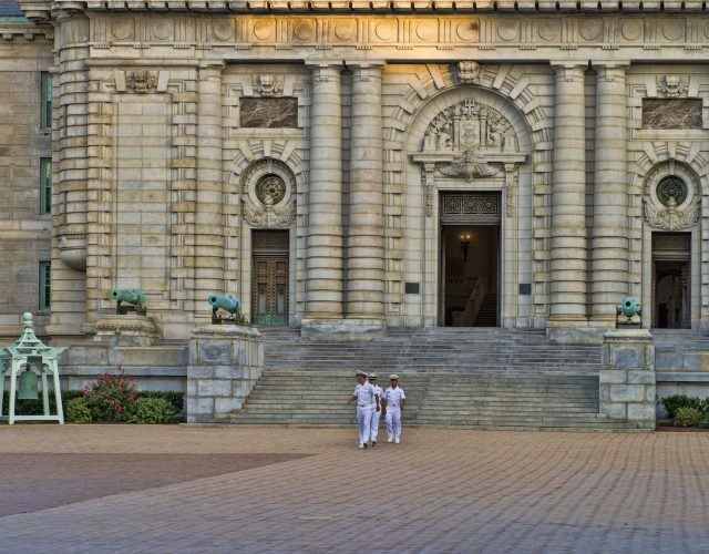 Naval Cadet midshipmen in uniform walk in front of Bancroft Hall at the U.S. Naval Academy