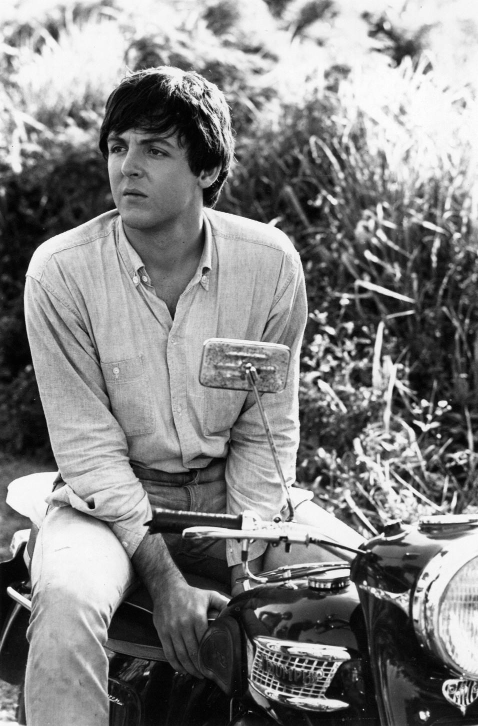 Paul McCartney of The Beatles sitting astride his motor bike, 1965.
