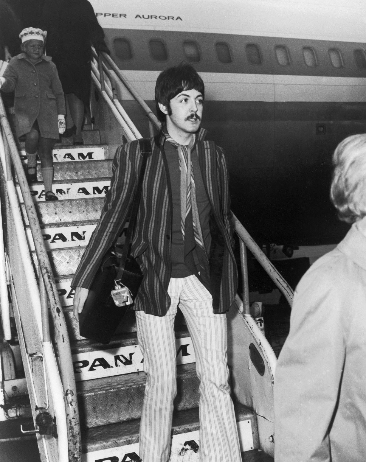 Paul McCartney of the Beatles steps off a Pan Am flight at London Airport