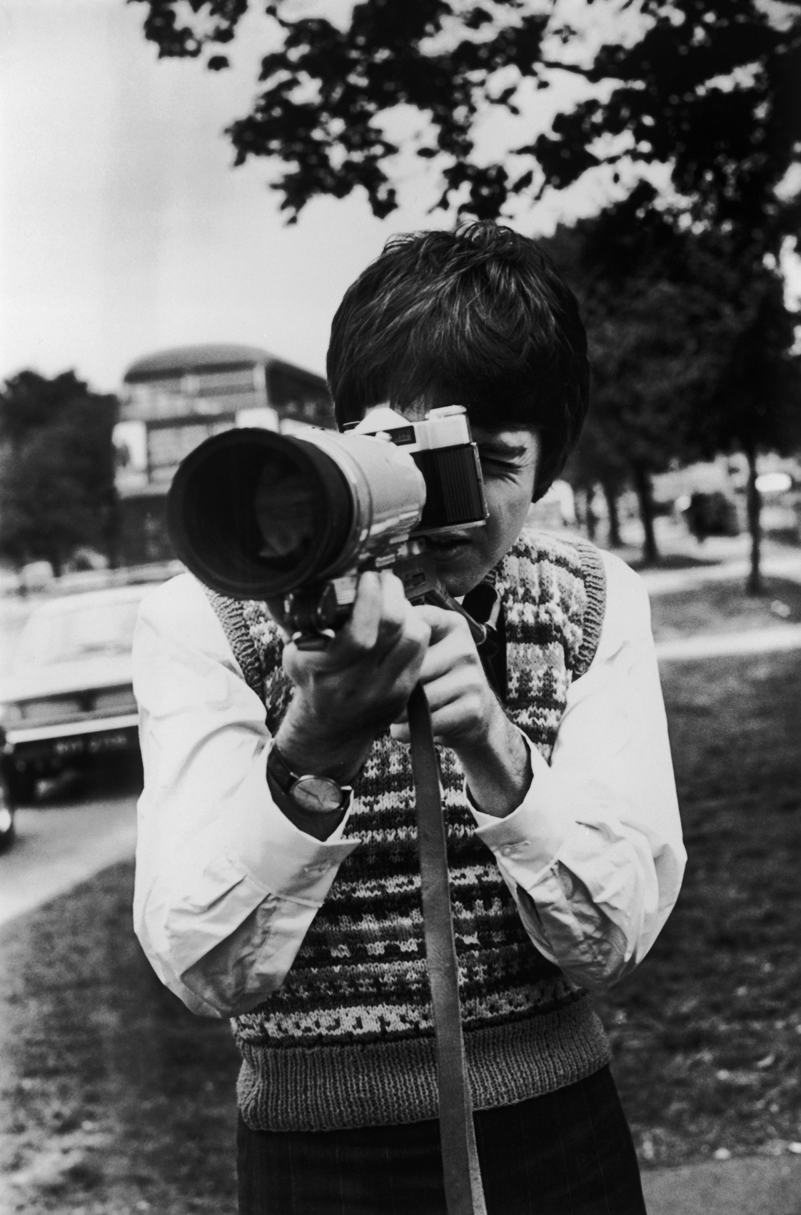 Paul McCartney takes some shots with a Russian Zenit Photo-Sniper camera outfit while waiting for the Magical Mystery Tour bus.