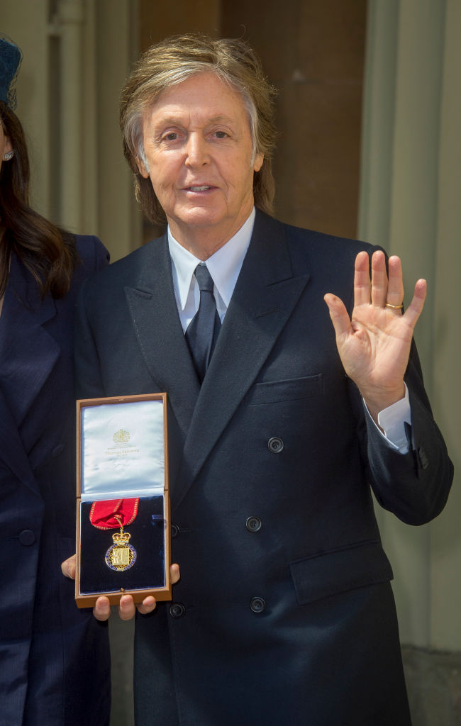 Sir Paul McCartney poses following an Investiture ceremony