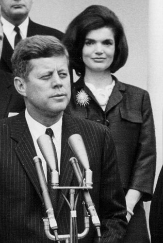 President John F. Kennedy speaks during a press conference as First Lady Jackie Kennedy looks on