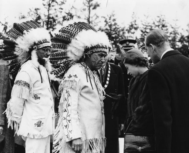 Princess Elizabeth and Prince Philip greet a group of Native American Chiefs at Fort William in Canada