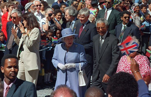 Queen Elizabeth II and President Nelson Mandela walk from office of the president to parliament in Cape Town