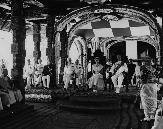 Queen Elizabeth II and Prince Philip listen to the Adigar, Sir Tikiri Bandara Panabokke II in Kandy, Ceylon, later Sri Lanka