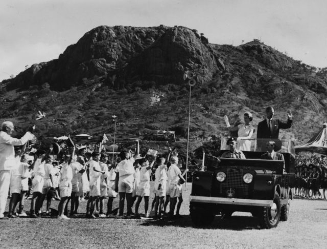Queen Elizabeth II and Prince Philip wave from the back of their Land Rover in Bundaberg, Australia