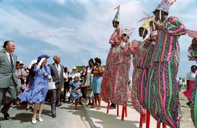 Queen Elizabeth II watches Anguillan boys on stilts