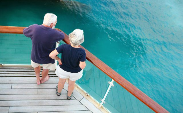 Senior couple watching ocean from cruise ship's deck