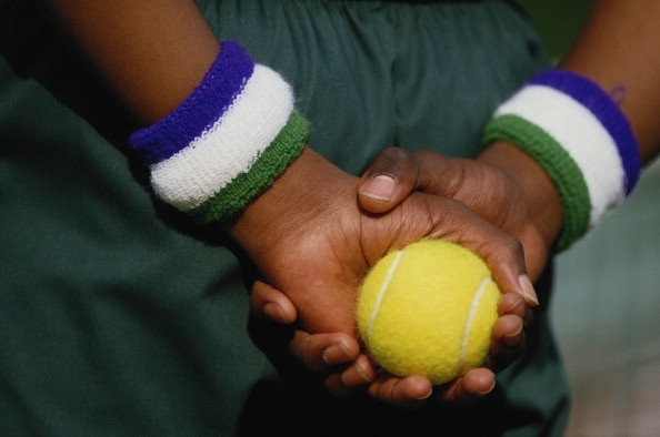 A ball boy with his Wimbledon sweatbands holds a tennis ball