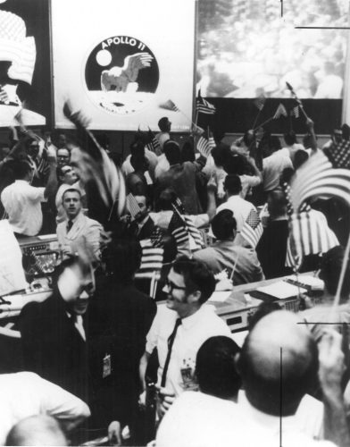 The Mission Operations Control Room in the Mission Control Center at the NASA Manned Spacecraft Center celebrates the success of Apollo 11