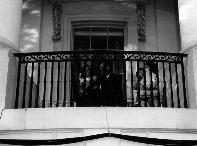 The President and Mrs. Kennedy sit with their children in the South Portico