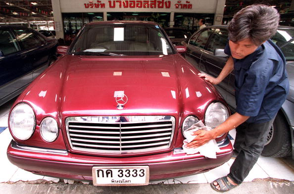 A Thai worker polishes a used Mercedes at a secondhand car market in Bangkok 13 July 1999