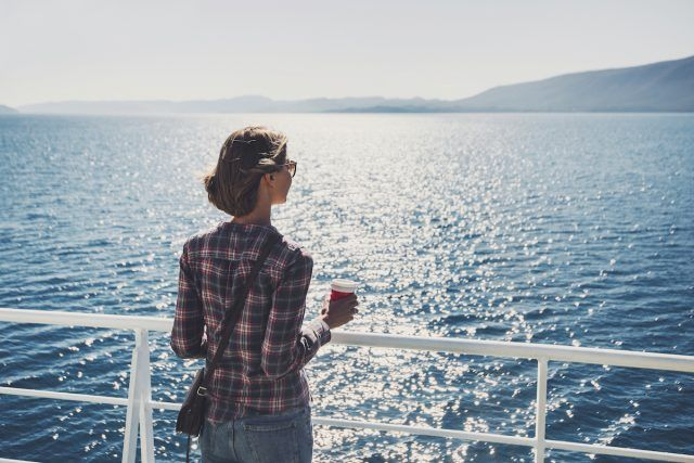 Young woman with a cup of coffee on a cruise ship or ferry