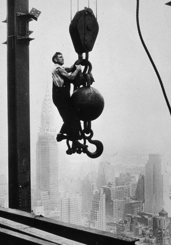 A construction worker stands on crane pulley counterweight during the construction of the Empire State Building
