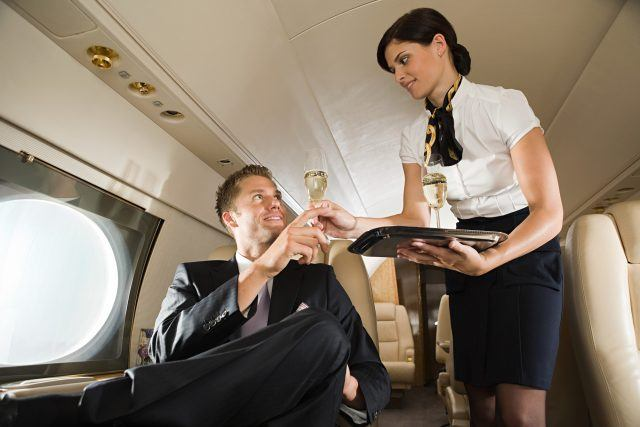 A flight attendant hands champagne to a passenger