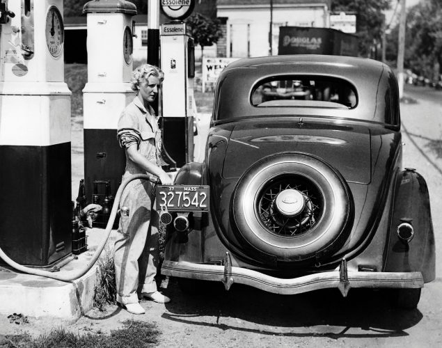 A fuel pump employee fills a car at a gas station in 1937