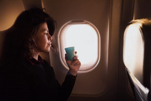 A passenger holds a cup of soda during a flight