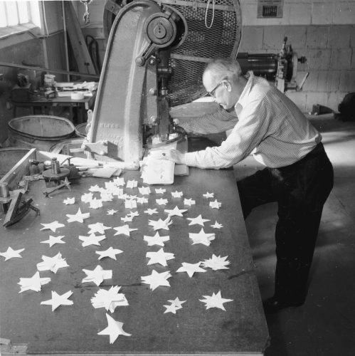 A star cutter making stars of various sizes to be sewn on to American flags at the Abacrome factory