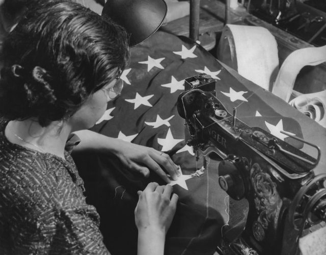A woman sews the stars onto an American flag in the 1950s