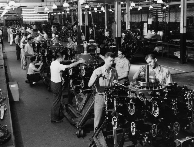 American factory employees work on rotary engines for aircraft