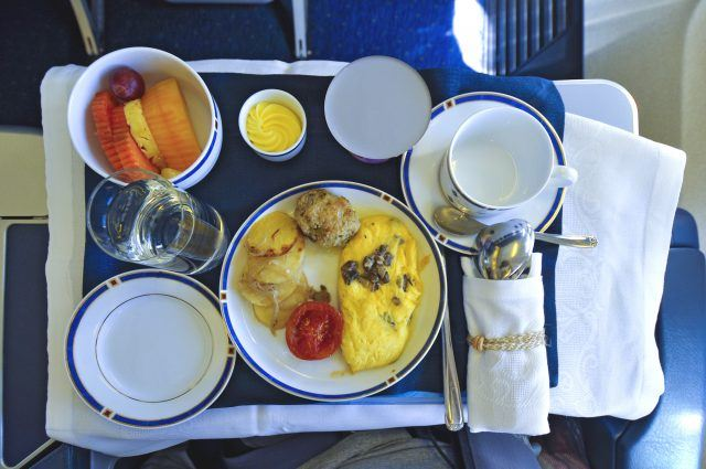 An airline meal with omelet and fruit